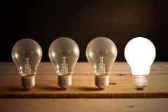 Light bulb lamps. Glowing bulb uniqueness concept on brown wooden background Royalty Free Stock Photography