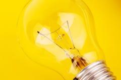 Light bulb lying on yellow background Stock Photos