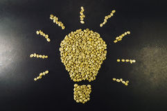 Light bulb made up of unroasted coffee beans, on black background Stock Photos