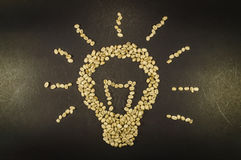 Light bulb made up of unroasted coffee beans, on black background Stock Images
