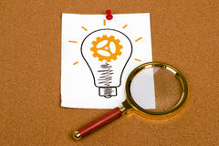 Light bulb and magnifier Stock Images