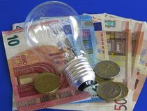 Light bulb and money. Light bulb, coins and bank-notes: business idea or energy saving concept Stock Photos