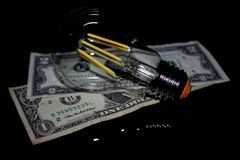 Light bulb on money. On a black background Royalty Free Stock Images