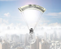Light bulb with money parachute Royalty Free Stock Photo