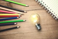 Light bulb with notepad and pencils on wooden background royalty free stock photography