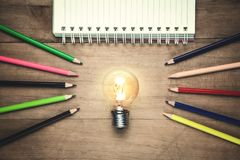 Light bulb with notepad and pencils on wooden background stock images
