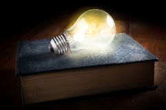 Light bulb on old book. Royalty Free Stock Photos