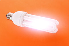 Light bulb on orange Stock Images