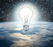 Light bulb over Earth on a background of the universe Stock Images