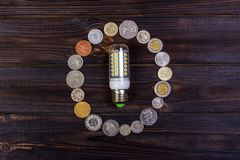 light bulb on over pile of coins - money, finance, savings concept and idea Royalty Free Stock Images