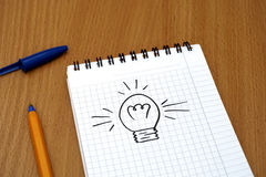 Light bulb painted on note pad with pen Stock Photo