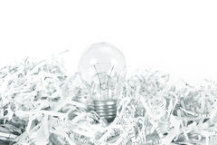 The Light bulb place on shredded recycled paper on white backgro. Light bulb place on shredded recycled paper on white background , idea innovation concept stock photo