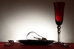 Light bulb in plate, cutlery and wineglass Stock Photography