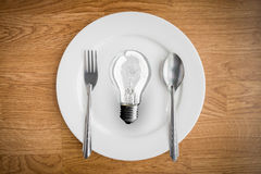 Light bulb in plate and fork and spoon on wooden table. Brain food Idea concept stock photography