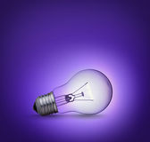 Light bulb on purple background Stock Photos