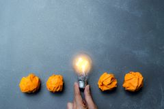 Hand holding light bulb put in the middle of orange papers it for idea,energy,solar concept. stock photography