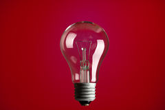 Light bulb on red background Stock Photography
