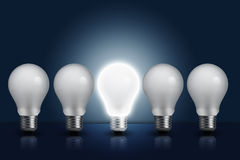 Light bulb in row with middle one turn on Royalty Free Stock Image