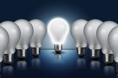 Light bulb in row with middle one turn on Royalty Free Stock Photos
