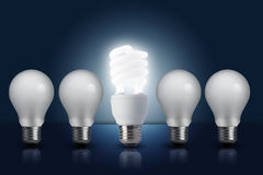 Light bulb in row with middle one turn on Stock Image