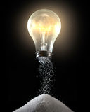 Light bulb and salt shaker. A light bulb with salt pouring out of the bottom stock images