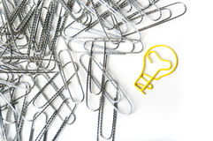 Light bulb shaped paper clip next to a pile of paper clips Stock Images