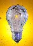 Light bulb in soda water. Electric light bulb in covered with bubbles in soda water, against an amber background Royalty Free Stock Image