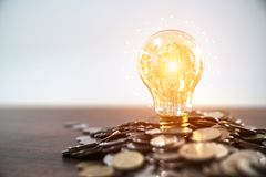 Light bulb and stack of coins in concept of savings and money gr stock photos