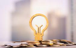 Light bulb and stack of coins in concept of savings and money growing or energy save. royalty free stock images