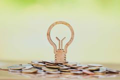Light bulb and stack of coins in concept of savings and money growing or energy save. stock photography
