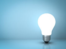Light bulb standing on blue background Stock Photos