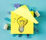 Light Bulb on a sticky note. On a blue background royalty free stock photo
