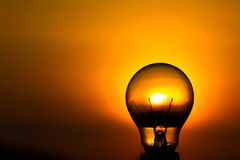 Light bulb with sunset sky background. Stock Images