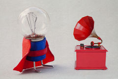 Light bulb in super hero costume. Vintage red color gramophone. Retro plastic toy. Old paper background and texture royalty free stock image