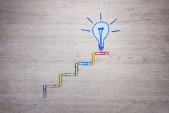 Light bulb symbol and colored staples on office desk. Royalty Free Stock Photos