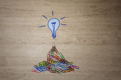 Light bulb symbol and colored staples on office desk. Royalty Free Stock Images