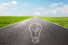 Light bulb symbol on long empty straight road. Highway. Concepts of environment, ecology, green energy, idea etc Royalty Free Stock Images
