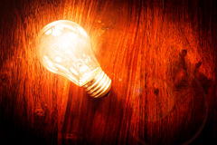 Light bulb on table. Bright light bulb on a wodden table Royalty Free Stock Photos
