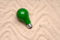 Light bulb tossed on the sand Stock Image
