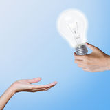 Light bulb transfer to another hand. Royalty Free Stock Image