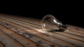 Light Bulb. Light transparent bulb isolated over a wood background. This is a 3D image Royalty Free Stock Images