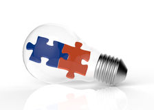 Light bulb and two puzzles Royalty Free Stock Photo