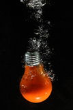 Light bulb underwater. A view of an electric incandescent light bulb descending through water Stock Images