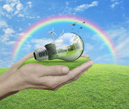 Light bulb with wind turbines, birds and forest inside in hands Royalty Free Stock Photo