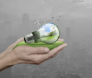 Light bulb with wind turbines and forest inside in hands Royalty Free Stock Photo