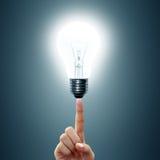 Light bulb on women's fingertips. Stock Image