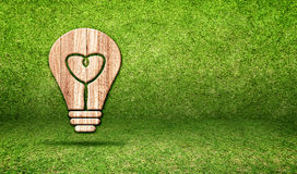 Light Bulb wood icon and heart shape inside in grass room,Eco co Royalty Free Stock Photos