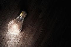 Light bulb on wooden surface . Mixed media Stock Images