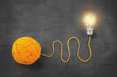 Light bulb with yarn concept idea on blackboard. Background Royalty Free Stock Photos