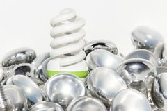 Light bulbs. Energy saving light bulb and a big number of traditional bulbs royalty free stock photography